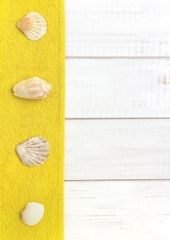 Fundo de madeira branco, conchas do mar toalhas amarelas