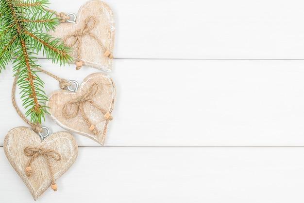 Fundo de madeira branco de natal com galhos de árvores de natal e corações