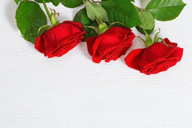 Fundo de madeira com borda floral. três rosas florescendo flores mentem na mesa de madeira.