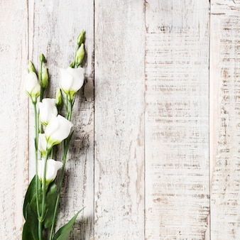 Fundo de madeira com buquê de flores brancas