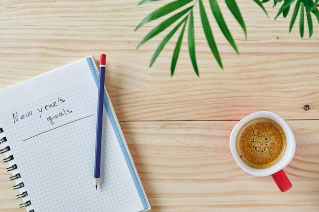 Fundo de madeira com caderno com as palavras metas de ano novo escritas em uma folha verde acima da imagem e uma xícara de café ao lado