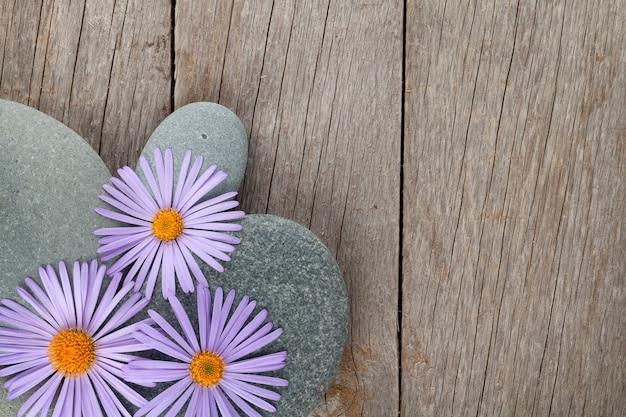 Fundo de madeira com flores azuis sobre pedras do mar e espaço de cópia