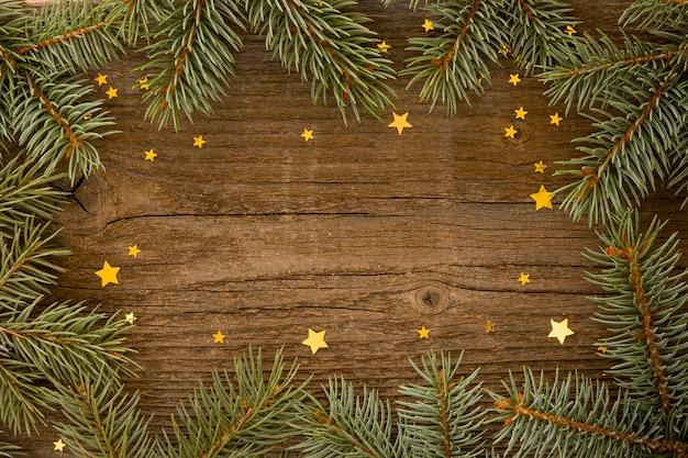 Fundo de madeira com folhas de pinheiro e estrelas