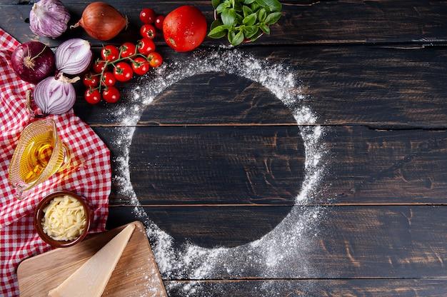Fundo de madeira com ingredientes para pizza. madeira cinza com guardanapo xadrez vermelho. copie o espaço. vista do topo