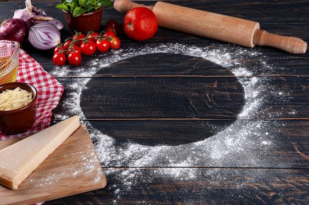 Fundo de madeira com ingredientes para pizza. madeira cinza com guardanapo xadrez vermelho. copie o espaço.