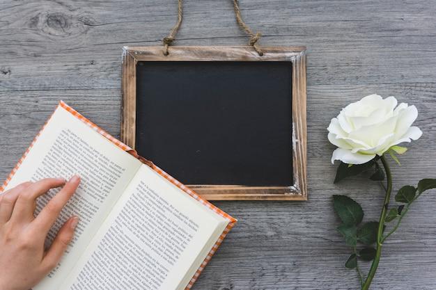 Fundo de madeira com livro aberto, ardósia e flor
