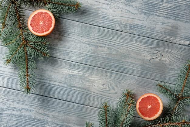 Fundo de madeira com ramos de abeto e metades de toranja. o conceito de um cartão de ano novo.
