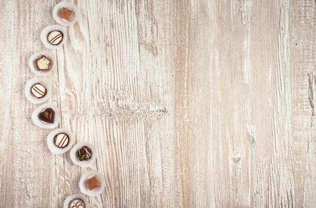 Fundo de madeira com uma linha de chocolates, espaço