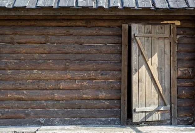 Fundo de madeira com uma porta. parede de madeira velha de uma casa rústica com textura e porta