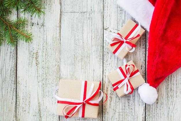 Fundo de madeira de férias de natal com ramos de abeto, chapéu de papai noel e caixas de presente