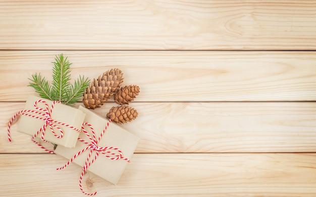 Fundo de madeira de natal com cones de caixas de presente e galho de árvore de natal