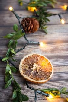 Fundo de madeira de natal com fatia de laranja seca, buxo, cones de abeto e guirlanda