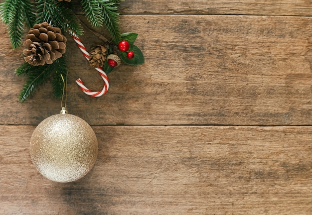Fundo de madeira de natal com folhas de pinho e cones, bugiganga e pirulito em vista superior plana leigos.
