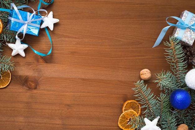 Fundo de madeira de natal com galhos de pinheiro, balões azuis e brancos, laranja seca, caixas de presente.