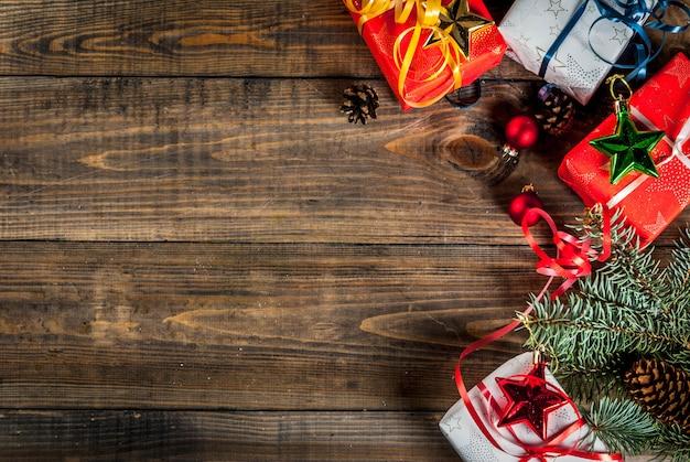 Fundo de madeira de natal com presentes de natal, galhos de árvores de abeto e decorações. copie o espaço