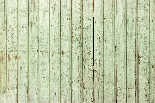 Fundo de madeira verde brilhante com pintura descascada e placas verticais