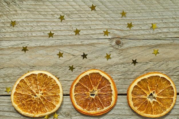 Fundo de madeira vintage com guirlanda de natal - fatias de laranja secas e confetes de ouro em forma de estrela. vista superior com espaço de cópia