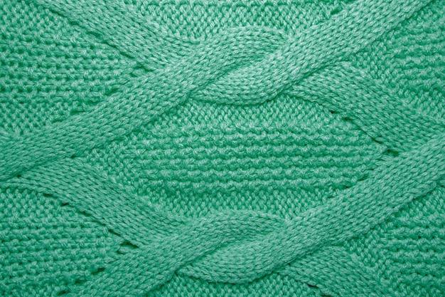 Fundo de malha de malha com um padrão de relevo. textura de suéter de lã verde close-up
