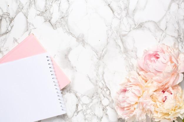 Fundo de mármore com flor de peônia branca e caderno feminino.