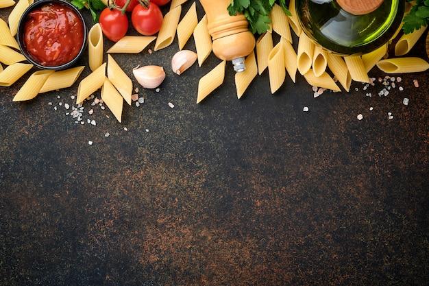 Fundo de massa. rigati de macarrão, molho de ketchup de tomate, azeite, especiarias, salsa e tomates frescos em uma mesa de ardósia escura. fundo de cozimento de alimentos. vista superior com espaço de cópia.