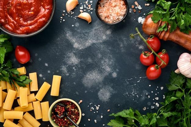 Fundo de massa. rigatoni de macarrão, molho de ketchup de tomate, azeite, especiarias, salsa e tomates frescos em uma ardósia escura, pedra ou fundo de concreto. vista superior com espaço de cópia.