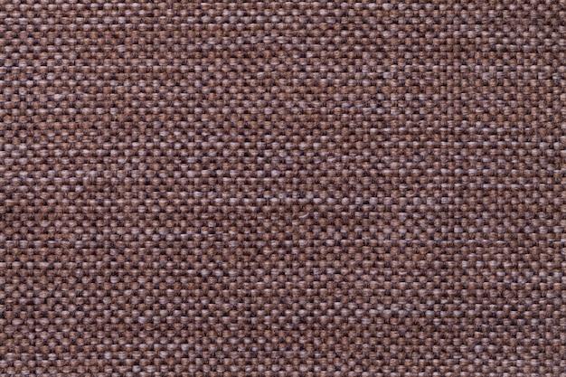 Fundo de matéria têxtil do marrom escuro com teste padrão quadriculado, close up. estrutura da macro de malha.