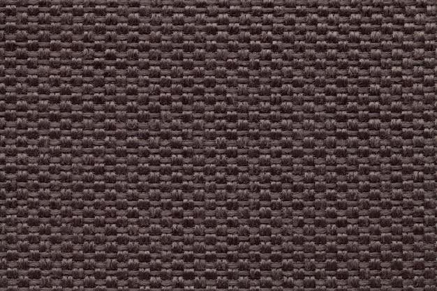 Fundo de matéria têxtil marrom com teste padrão quadriculado, close up. estrutura da macro de malha.