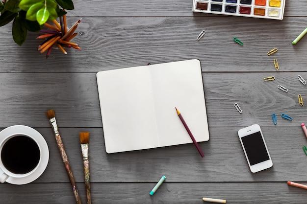 Fundo de mesa arte criativa com tintas de caderno, desenho educação, plana leigos