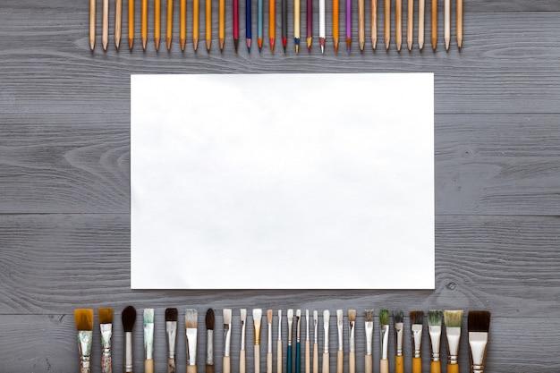 Fundo de mesa criativa com pincéis, lápis e papel para esboços