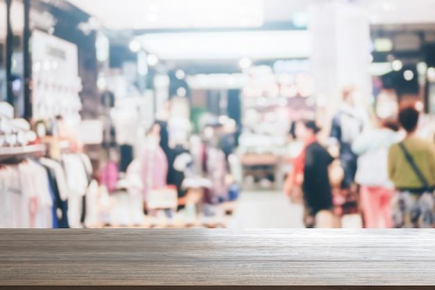 Fundo de mesa de madeira no fundo de produtos de montagem de shopping supermercado turva