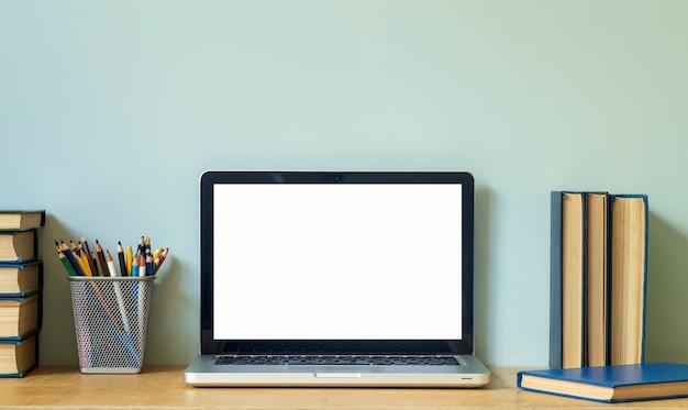 Fundo de mesa de mesa de escritório em casa. pc de tela do laptop vazio na mesa de madeira com livros para trabalho ou estudo. foto de alta qualidade