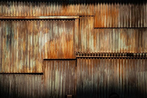 Fundo de metal ondulado de textura grunge escuro, superfície do aço enferrujado, área deteriorada da parede da favela