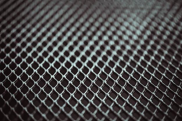 Fundo de metal. textura de treliça com grade de pequenas células. ponto de foco seletivo.