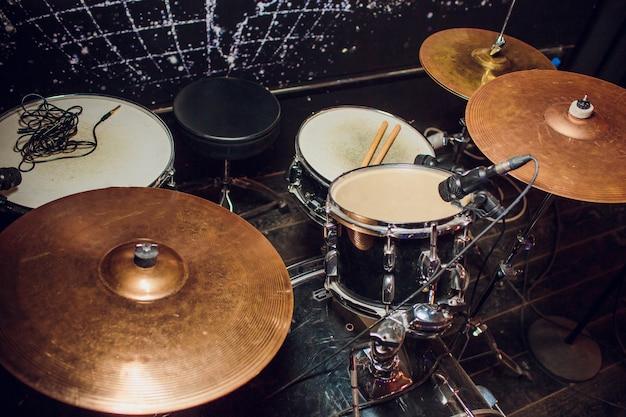 Fundo de música ao vivo em tons vintage, baterista toca com baquetas na bateria de rock