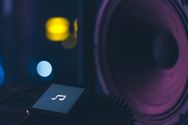 Fundo de música com telefone e com o ícone da música e coluna, conceito de tecnologia moderna, ouvindo música.