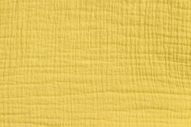 Fundo de musselina do algodão na cor amarela da mostarda.