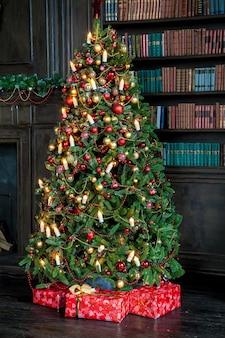 Fundo de natal. árvore de natal clássica verde decorada com bolas de natal e velas