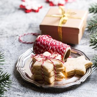 Fundo de natal. biscoito de gengibre festivo com fita, ramos de pinheiro
