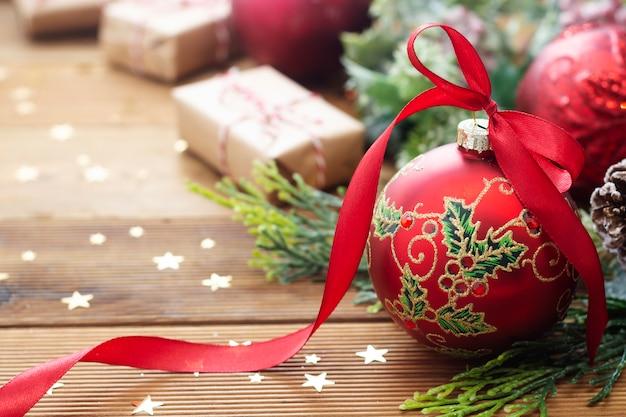 Fundo de natal. bugiganga linda vermelha com fita, ramos de abeto.