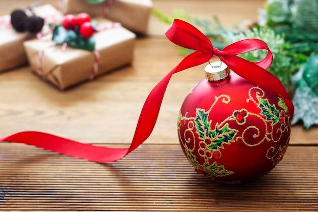 Fundo de natal. bugiganga linda vermelha com fundo de madeira da fita.