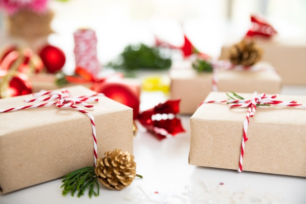 Fundo de natal. caixa de presente de natal com cones de bola e pinho vermelhos sobre fundo branco.