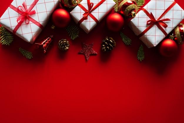 Fundo de natal. caixa de presente de natal com cones de bola e pinho vermelhos sobre fundo vermelho.