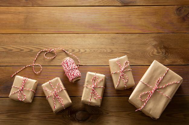 Fundo de natal. caixas de presente embrulhadas em papel ofício sobre fundo de madeira. vista superior, estilo rústico. copie o espaço.