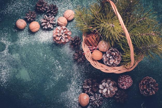 Fundo de natal. cesta com cones de abeto e galhos, nozes.
