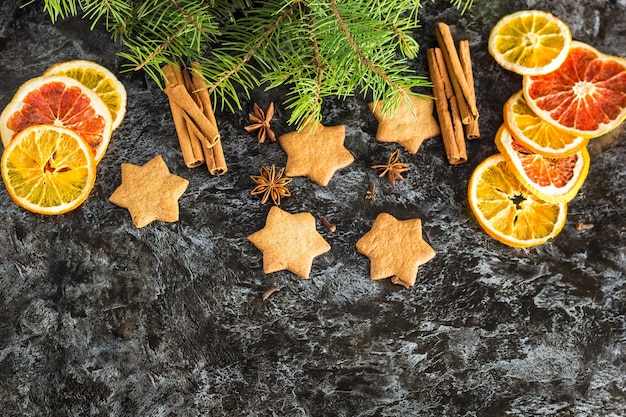 Fundo de natal com anis de canela e laranja seco de pinheiro e estrela de biscoitos de gengibre em fundo escuro com copyspace