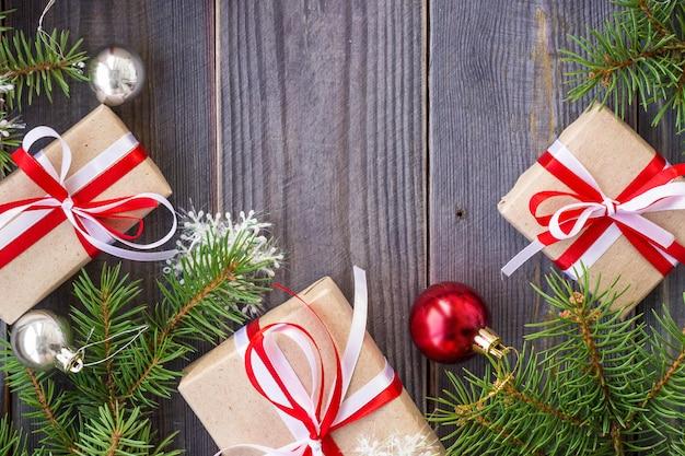 Fundo de natal com árvore do abeto e decorações e caixas de presente na placa de madeira