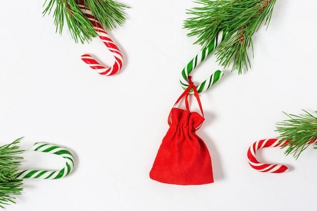 Fundo de natal com bastões de doces e presente em uma pequena sacola vermelha