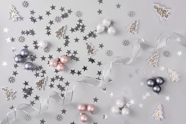 Fundo de natal com bolas de glitter rosa cinza pastel, estrelas, em cinza prateado. vista do topo. padrão de natal. ano novo.