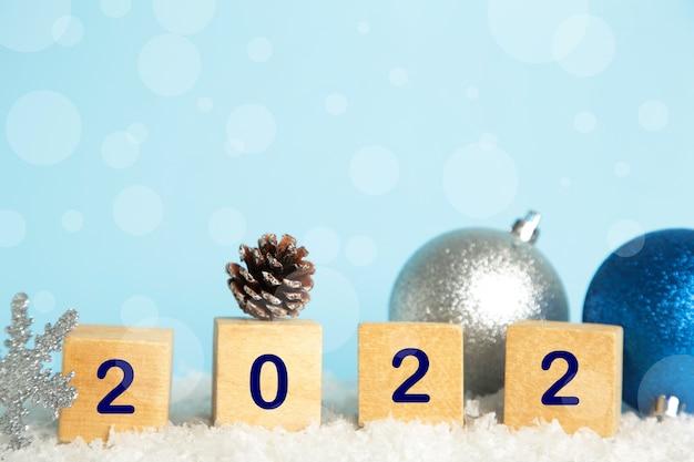 Fundo de natal com bolas de natal e algarismos 2022. conceito de ano novo em fundo azul.