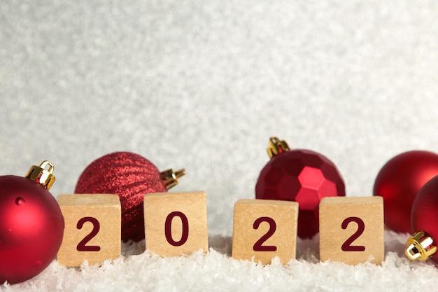 Fundo de natal com bolas de natal e algarismos 2022. conceito de ano novo em fundo branco.